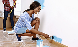 Lady painting a wall at home